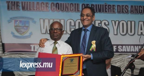 Vishnu Lutchmeenaraidoo, tout sourire, remettant un souvenir à M. Vengrasamy Rungasamy, ancien président du conseil de district de Grand-Port–Savanne. © DAREN MAUREE