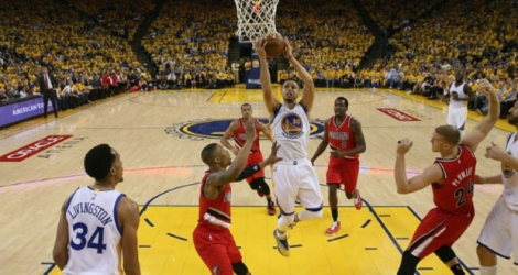 Le meneur de jeu des Golden State Warriors Stephen Curry (c) tente un panier face aux Portland Trail Blazers, le 11 mai 2016 à Oakland en Californie.