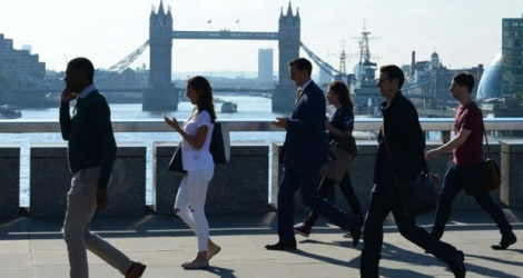 Des employés de la City de Londres traversent le London Bridge.