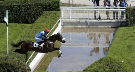 Le jockey britannique James Reveley en selle sur So French saute la rivière des tribunes, le 21 mai 2017.