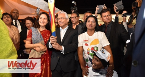 Prime Minister Pravind Jugnauth holding the flame of the IOIGs, moments after Arvind Jugroo (with the cap) – who has been suffering from a disability since birth – handed it to him. © Krishna Pather
