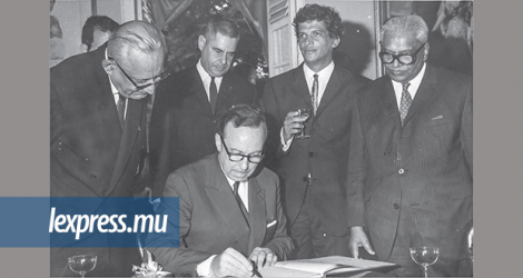 Sir Harilal Vaghjee, Raphael Leonard Touze, France's first Ambassador to Mauritius, Sir Gaetan Duval and Sir Seewoosagur Ramgoolam look on as Michel Debré signs a document.