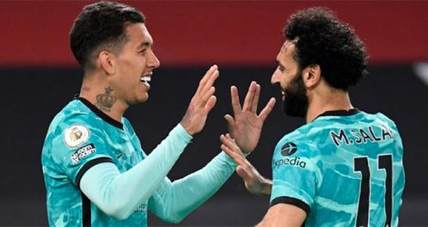 La joie du milieu de terrain brésilien de Liverpool, Roberto Firmino, félicité par l'Egyptien Mohamed Salah, après avoir marqué le 3e but face à Manchester United, lors de leur match de Premier League, le 13 mai 2021 au stade d'Old Trafford à Manchester. afp.com - PETER POWELL